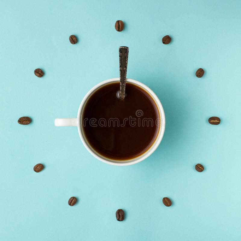 Coffee cup and roasted beans arranged as clock face on blue background, top view. Coffee time symbol. Interesting idea energy and. Refreshment concept stock photo