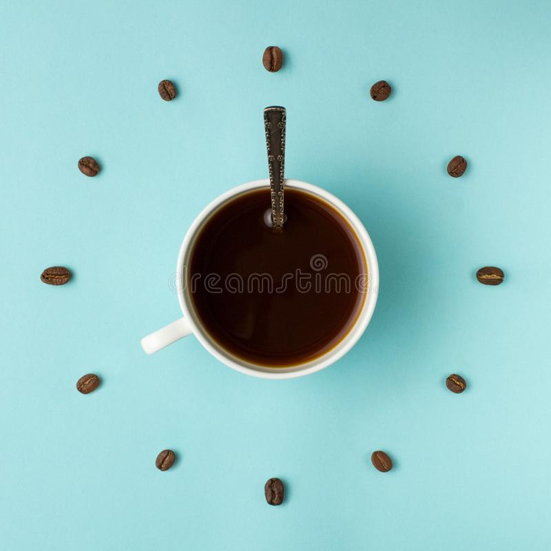 Coffee cup and roasted beans arranged as clock face on blue background, top view. Coffee time symbol. Interesting idea energy and. Refreshment concept stock photos