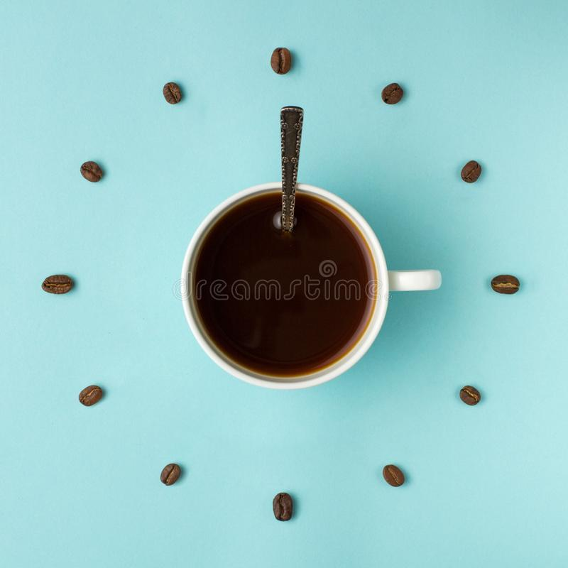 Coffee cup and roasted beans arranged as clock face on blue background, top view. Coffee time symbol. Interesting idea energy and. Refreshment concept stock image