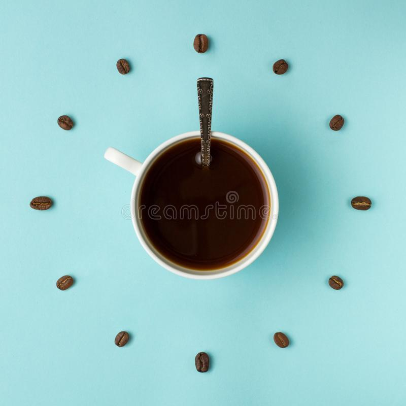 Coffee cup and roasted beans arranged as clock face on blue background, top view. Coffee time symbol. Interesting idea energy and. Refreshment concept royalty free stock images