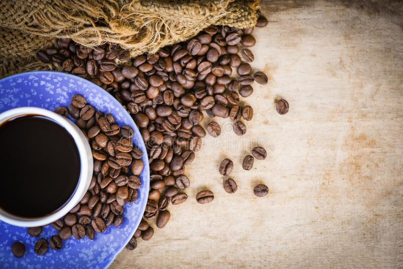 Coffee cup on roasted coffee beans sack and rustic wood background top view stock image