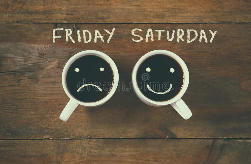 Coffee cup with sad and happy faces next to friday saturday phrase background. vintage filtered. happy weekend concept royalty free stock image