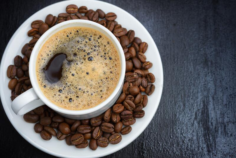 Coffee cup and saucer on a wooden table. Dark background royalty free stock image