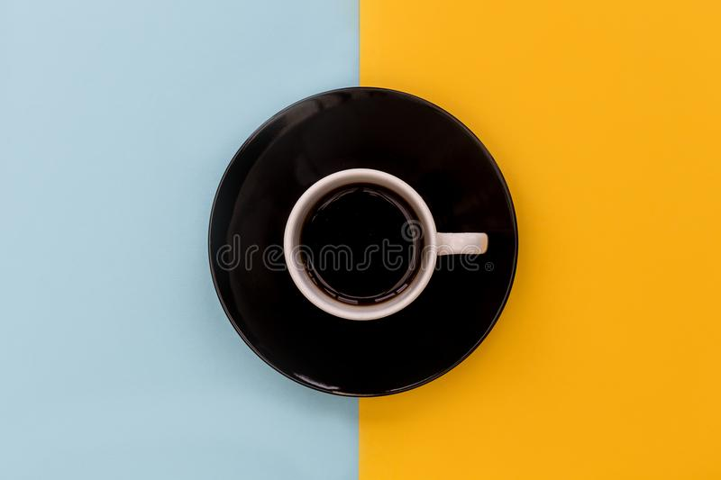 Coffee cup + saucer on yellow and blue background royalty free stock photos