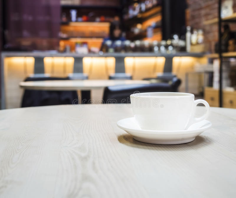 Coffee cup in Shop cafe with blurred counter bar. Background royalty free stock photos