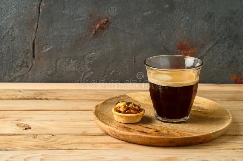 Coffee cup and small caramel nut tart on wooden table. Coffee cup and small  caramel nut tart on wooden table royalty free stock images