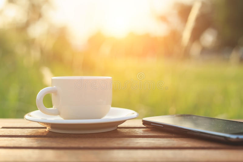 Coffee cup and smartphone on the table in the morning. Coffee cup and smartphone on the table stock image