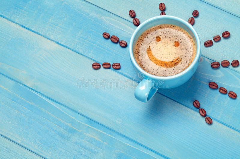 Coffee cup with smiley face on blue wooden table stock photo