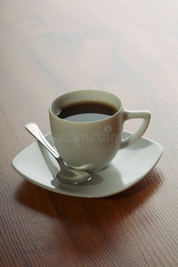 Coffee cup with spoon. White coffee cup with spoon on wooden background stock images
