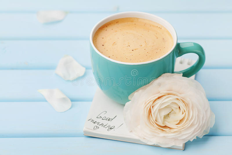 Coffee cup with spring flower and notes good morning on blue rustic background, breakfast. On Mothers day or Womens day stock image