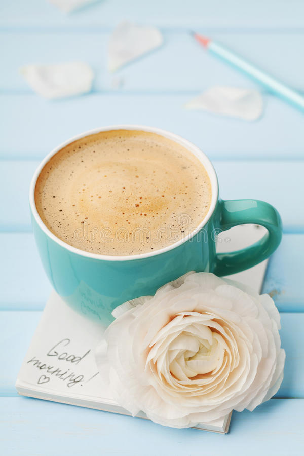 Coffee cup with spring flower and notes good morning on blue rustic background, breakfast royalty free stock photo