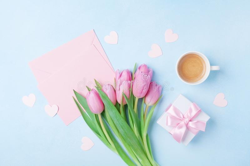 Coffee cup, spring tulip flowers, gift box and pink paper card on blue pastel table top view. Greeting for Womans or Mothers Day. Flat lay royalty free stock images