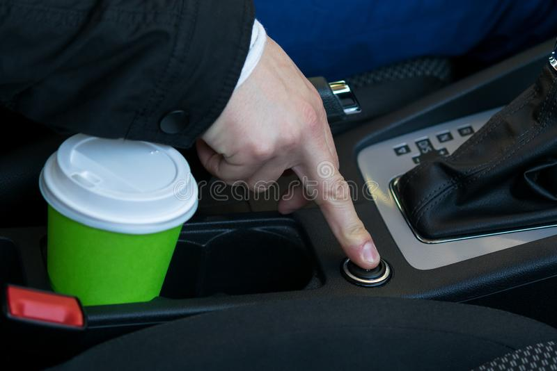 Coffee cup in a stand in the passenger compartment, the driver's hand turns on the cigarette lighter stock photos