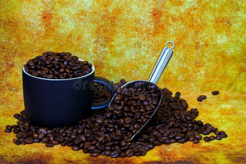 Coffee cup and steel scoop filled with coffee beans on grunge background stock images