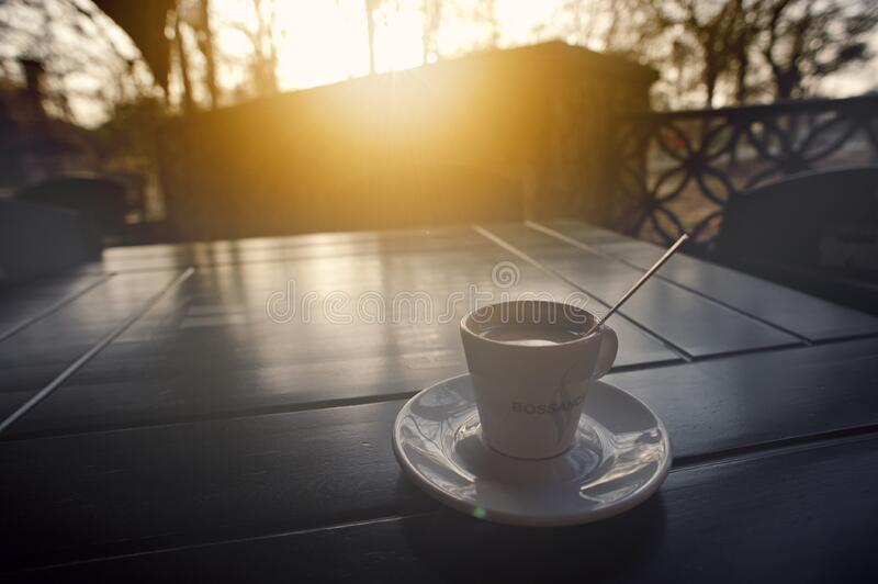 Coffee cup on table at sunrise stock image