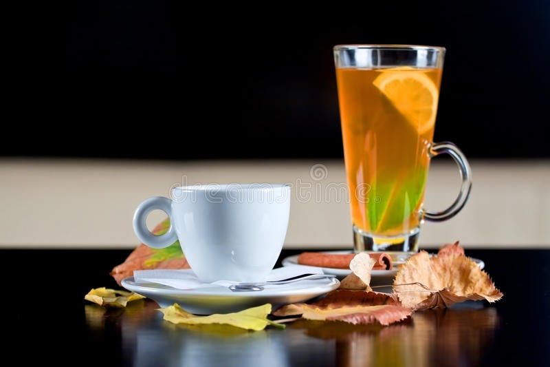 Coffee cup and tea glass next to autumn leaves. Cup of coffee and glass of tea next to autumn leaves on dark wood table. Selective focus stock photos