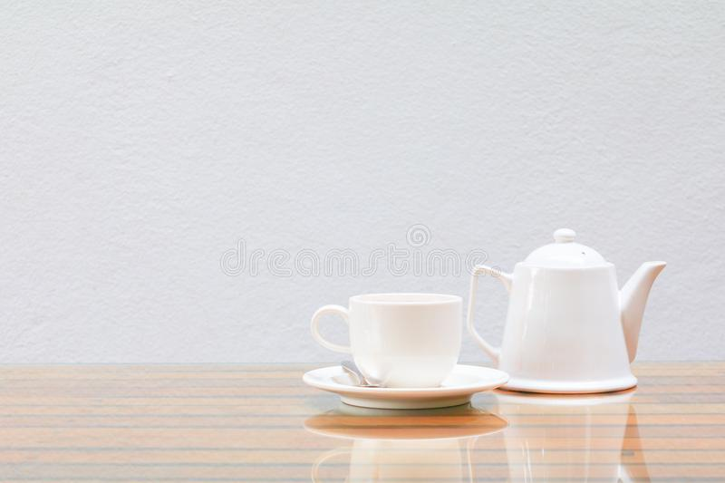 Coffee cup and teapot white On the glass table wooden and a cement wall background. Copy space royalty free stock photo
