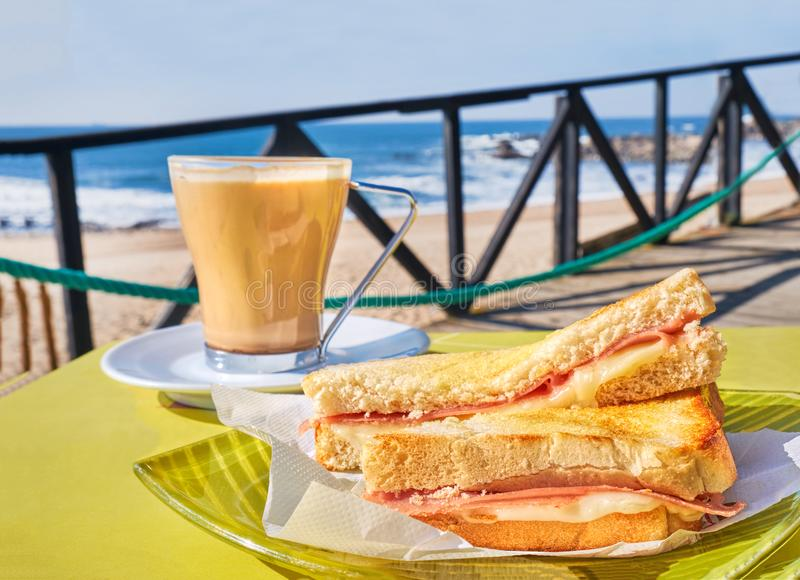 Coffee cup and toasts with cheese and ham on table in cafe, terrace with sea waves view. Traditional Portuguese snack royalty free stock photo