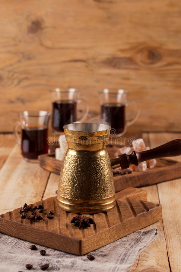 Coffee cup and turk with roasted beans on a wooden table. Vintage aroma concept on wooden background. stock image