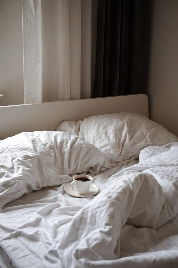 A coffee cup on a white bed. Pillow stock photos