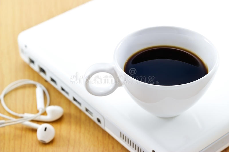 Coffee cup on white laptop and earphone, relax time and business. Soft focus stock image
