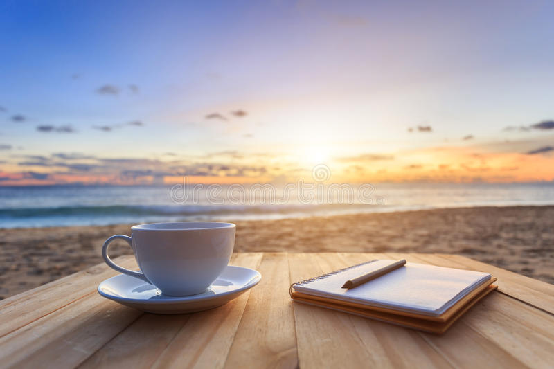 coffee cup on wood table at sunset or sunrise beach royalty free stock photo
