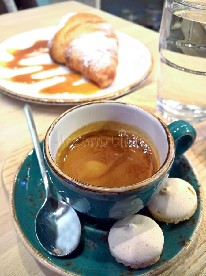 Coffee in a cup on a wooden table. Coffee with milk in a cup and a glass with water on a wooden table stock images