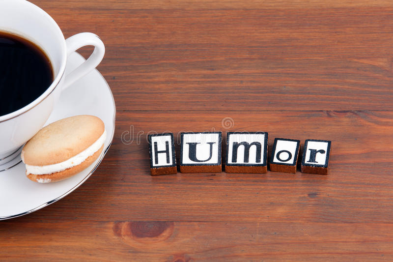 Coffee cup on a wooden table and text - Humor.  stock photography