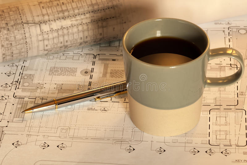 Coffee cup with work plan. Coffee cup on architectural work plan stock photos