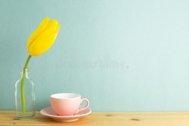 Coffee cup with yellow tulip flower in glass bottle on wooden table with mint green background. Floral arrangement, copy space stock images