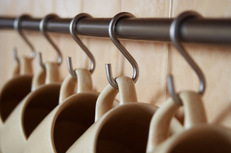 Coffee cups. Five coffee cups hanging in a row. Shallow DOF royalty free stock photo
