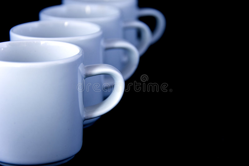 Coffee cups. Four white coffee cups or mugs in raw - against black background stock photo