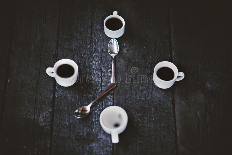Coffee cups aranged as a clock face on a wooden black background. Four espresso mugs like a symbol of time with two spoons. Time f royalty free stock photo
