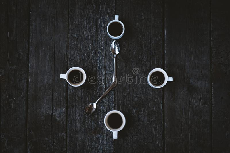 Coffee cups aranged as a clock face on a wooden black background. Four espresso mugs like a symbol of time with two spoons. Time f royalty free stock photography