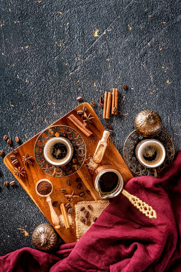Coffee cups with coffee beans and pot. Vintage coffee arrangement on black background royalty free stock photography