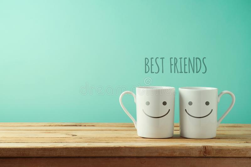 Coffee cups with funny faces on wooden table stock images