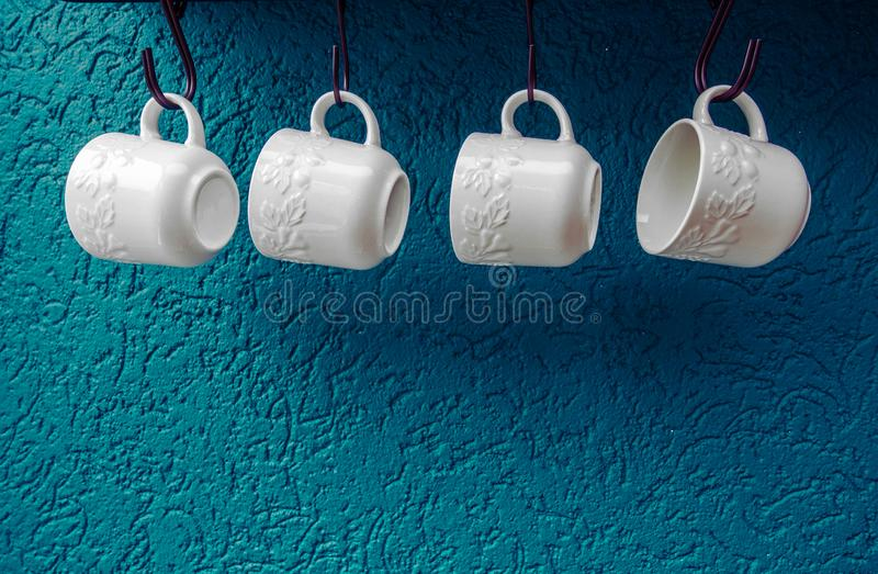 Coffee cups hanging on hooks of blue kitchen wall modern interior stock photos