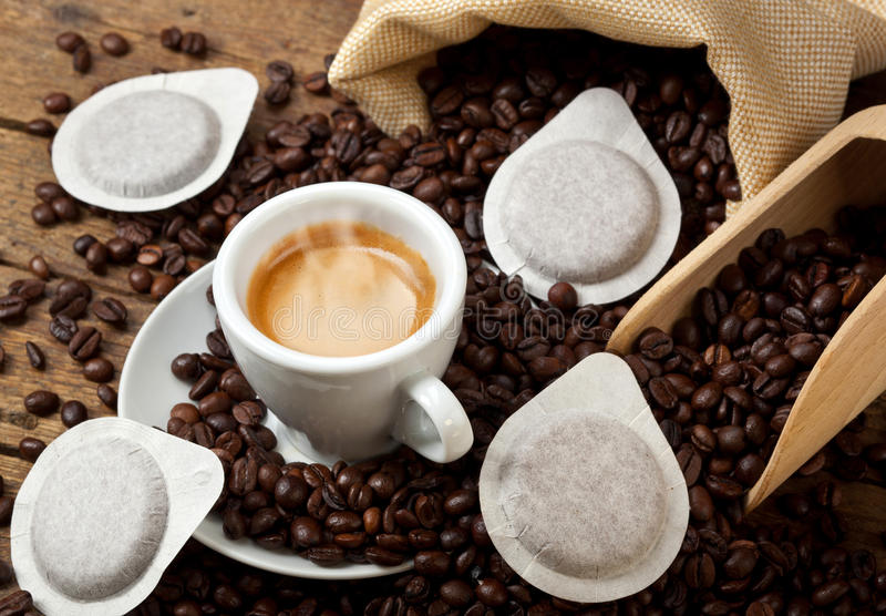 Coffee cups with pods. On rustic table royalty free stock photography