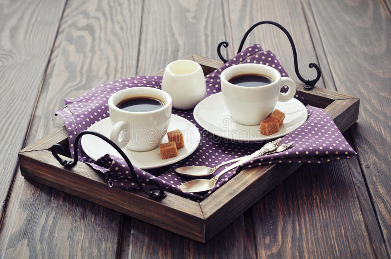 Coffee in cups. With spoon and milk on vintage wooden tray stock photo