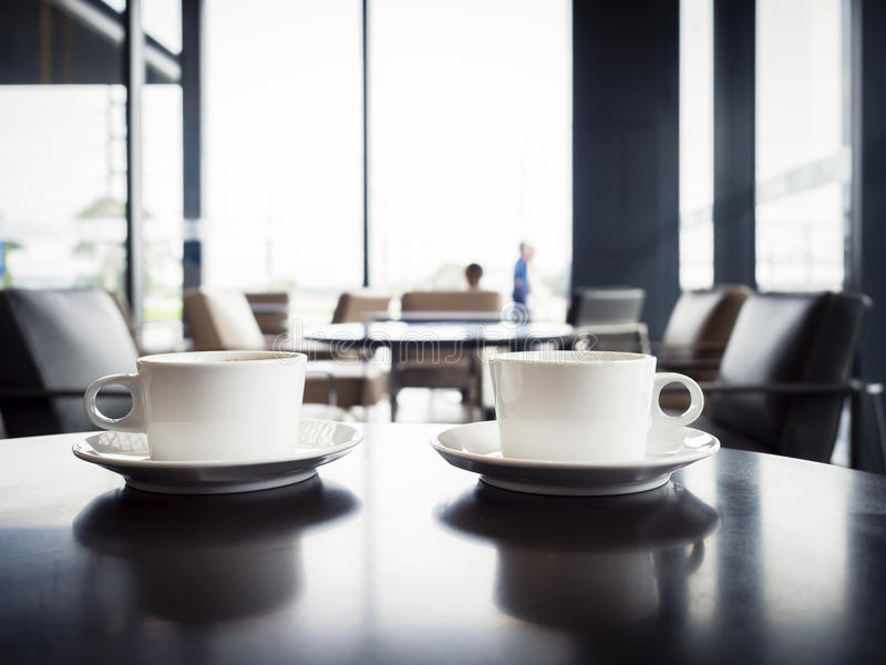 Coffee cups on table with blurred people in Restaurant shop cafe. Lounge Interior seats stock photos