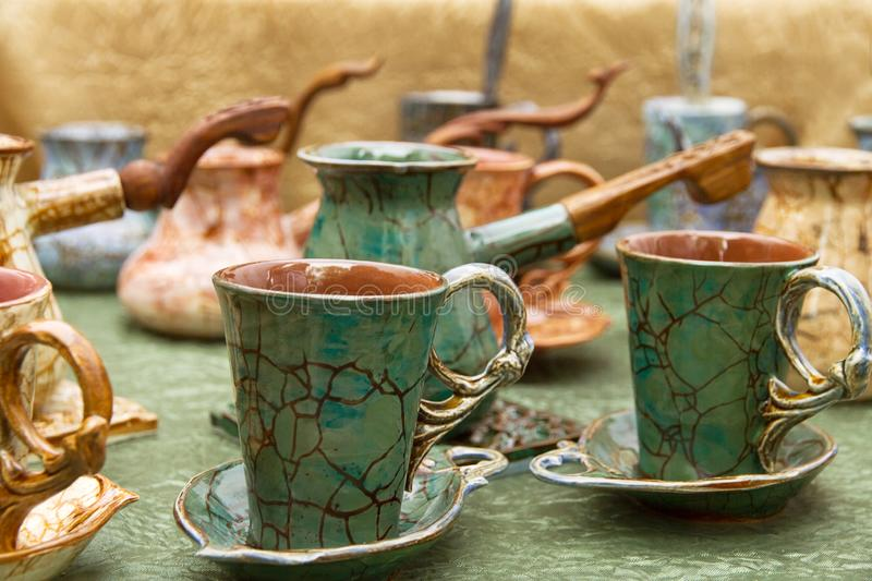 Coffee cups and turk with pattern of craquelure. Coffee cups and turk brown green with pattern of craquelure is introduced stand on the table royalty free stock images