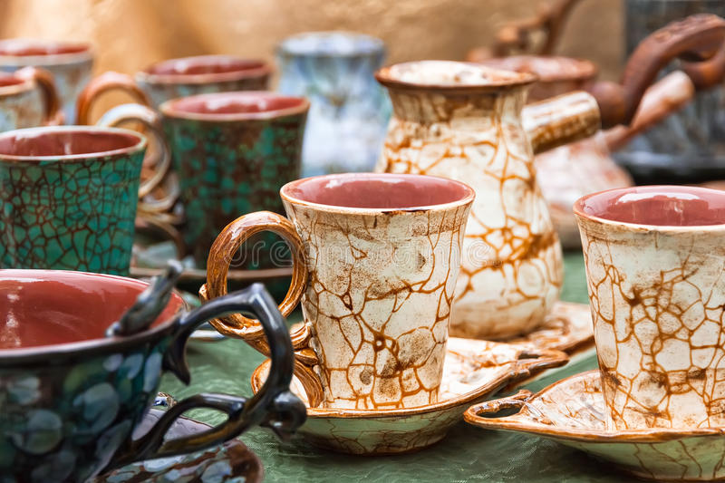 Coffee cups and turk with pattern of craquelure. Coffee cups and turk brown green with pattern of craquelure is introduced stand on the table royalty free stock image