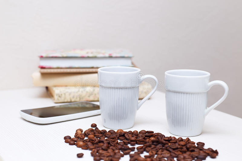 Coffee cups in white and coffee grains at the table stock photos