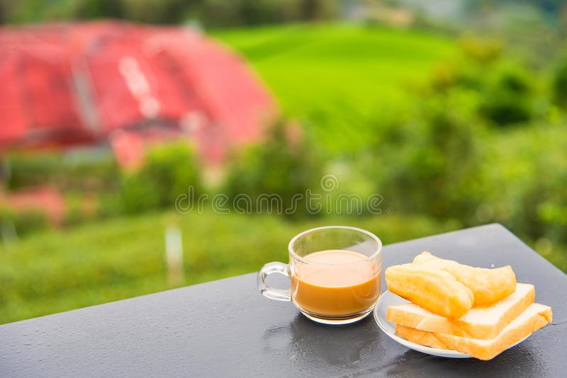 Coffee and deep-fried dough stick on wood table at the tea plantation in morning time.Thailand. Asia asian background bean beverage black bread break breakfast stock photography