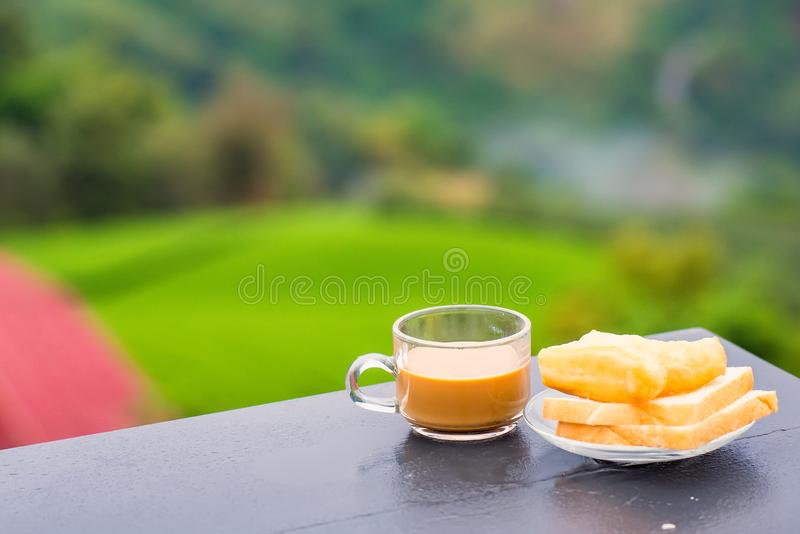 Coffee and deep-fried dough stick on wood table at the tea plantation in morning time.Thailand. Asia asian background bean beverage black bread break breakfast stock photo