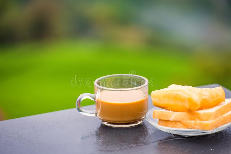 Coffee and deep-fried dough stick on wood table at the tea plantation in morning time.Thailand. Asia asian background bean beverage black bread break breakfast stock photos