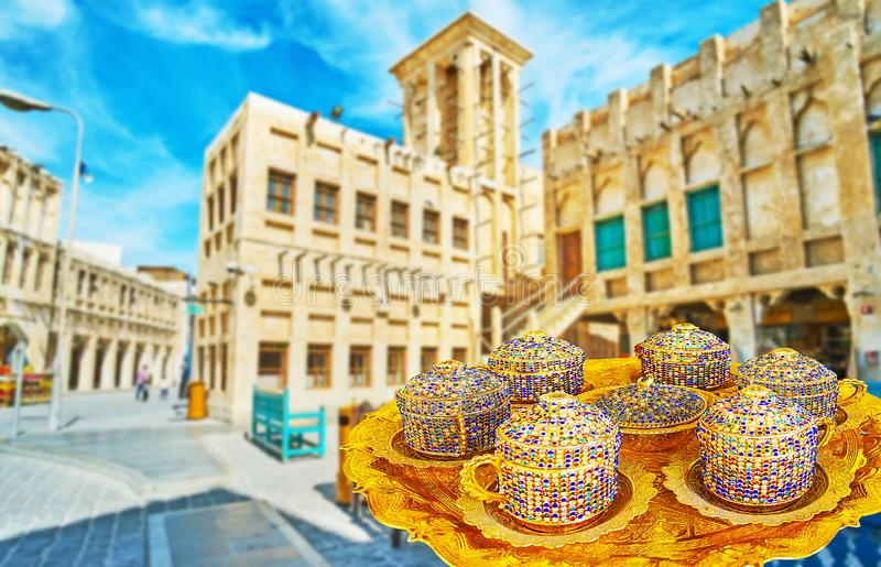 Coffee delivery in Souq Waqif, Doha, Qatar. Waiter delivers coffee in authentic Ottoman-styled cups, decorated with shiny glass inlays and standing on the golden royalty free stock photos