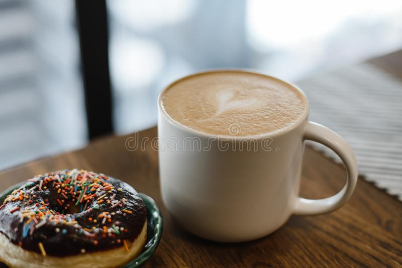 Coffee with a drawn heart and milk on a wooden table. In a coffee shop. Chokolate donut with scattering on the table next to the coffee royalty free stock photography
