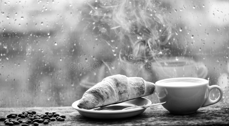 Coffee drink with croissant dessert. Enjoying coffee on rainy day. Coffee time on rainy day. Fresh brewed coffee in royalty free stock image