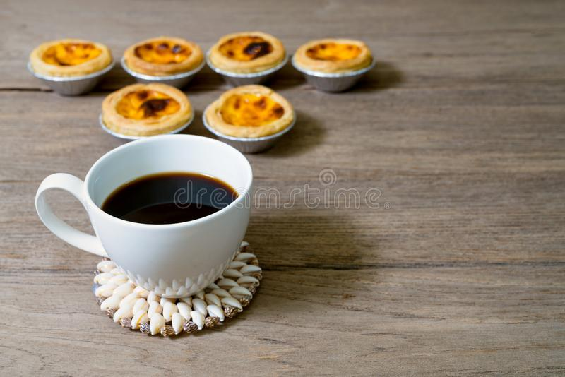 Coffee with egg tart in aluminum foil cup on wood table.  stock photos